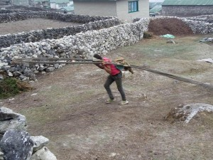 On back - Building materials transported by porters from Syanboche airport to Kunde